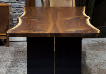 Live edge dining conference table in solid book-matched Black Walnut live edge slabs on massive black plate steel legs, on display at our retail furniture store in Chicago area, East Dundee, Illinois