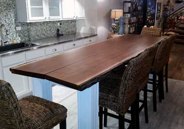 Large live edge dining table in solid Black Walnut on custom base and legs, displayed at retail furniture store in East Dundee, IL