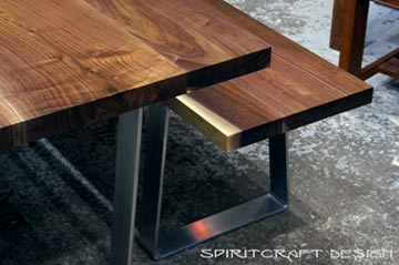 Solid hardwood dining table and bench from slabs of kiln dried Black Walnut with mid century modern style stainless steel trapezoid legs at The Great Spirit Furniture Company showroom in East Dundee, Illinois